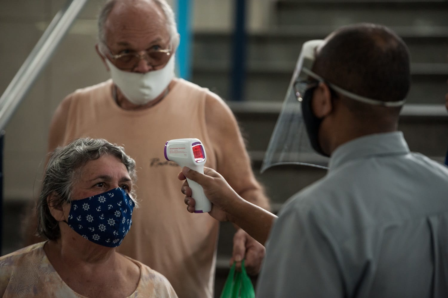 """An elderly couple are seen during the temperature temperature to enter the shopping center known as """"Mercadão de Madureira"""", located in the north of the city of Rio de Janeiro,  on June 19, 2020. Local authorities start a second of the six stages of easing social and commercial isolation, following distance social security measures to prevent the spread of COVID-19 (coronavirus) or which allows only 30% of the capacity for cases. (Photo by Allan Carvalho/NurPhoto)"""